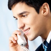 18658712-portrait-of-young-smiling-businessman-or-call-center-worker-with-phone-at-office.jpg